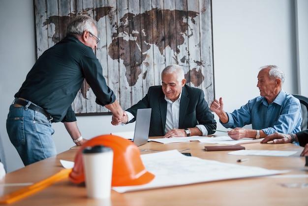 Händeschütteln machen. ein gealtertes team älterer geschäftsmannarchitekten trifft sich im büro.