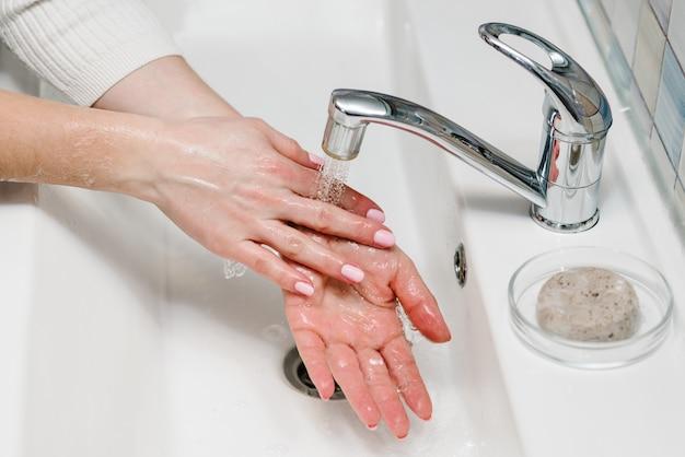Händewaschen. coronavirus prävention. waschen sie ihre hände mit antibakterieller seife, warmem fließendem wasser und reiben sie nägel und finger im waschbecken. epidemie covid-19. prävention von grippeerkrankungen.