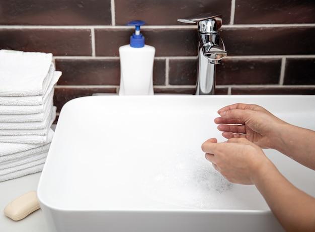 Händewaschen mit fließendem wasser im badezimmer. das konzept der persönlichen hygiene und gesundheit.