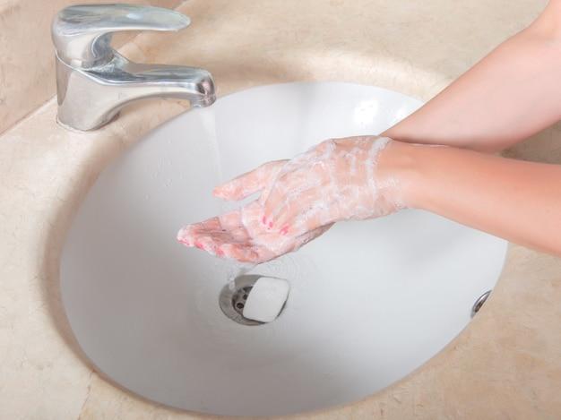 Händewaschen mit seife unter dem wasserhahn