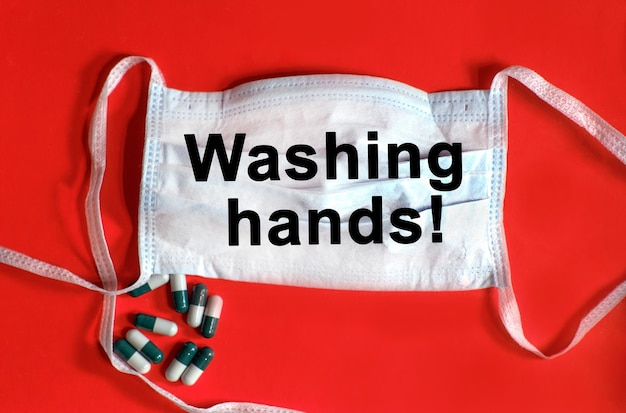 Händewaschen - text auf einer schützenden gesichtsmaske, tabletten auf rotem grund