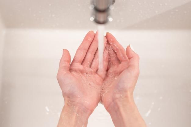 Händewaschen zur vorbeugung des coronavirus-ausbruchs frauen halten handflächen im wasserfluss im waschbecken im badezimmer