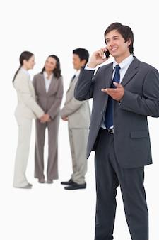 Händler, der am telefon mit team hinter ihm spricht