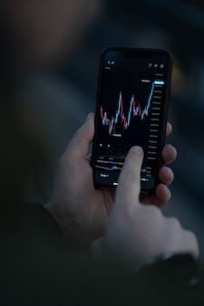 Händler, der börsendaten in der mobilen app für den online-handel überprüft. männliche hand, die den smartphone-bildschirm mit echtzeit-forex-chart berührt, finanznachrichten liest und den preisfluss analysiert, selektiver fokus