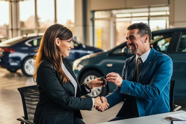 Händler, der dem neuen inhaber schlüssel gibt und hände in der automobilausstellung oder im salon rüttelt.