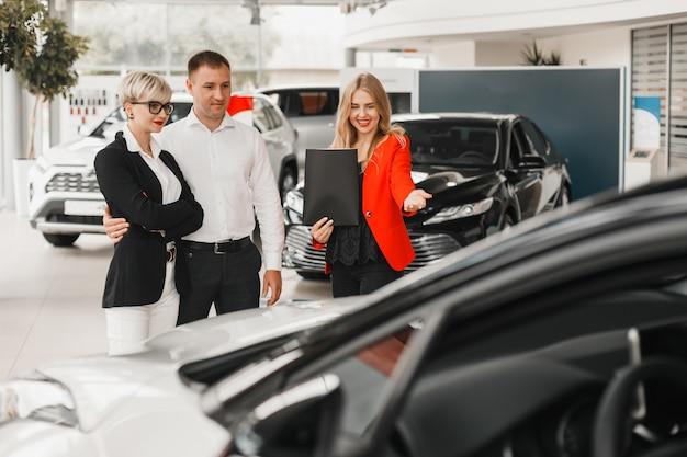 Händler, der ein auto zeigt. paar wählen und kaufen das auto.