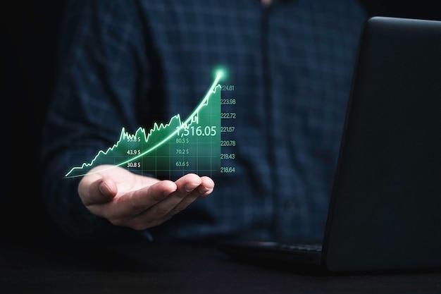 Händler, der ein grünes diagramm mit pfeil hält und laptop-computer für die analyse von börseninformationen verwendet, anlagekonzept.