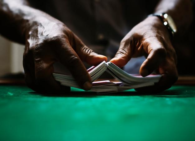 Händler, der einen kartenstapel im kasino mischt