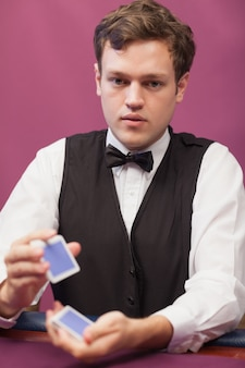 Händler, der in einem kasino sitzt, während karten schlurfend