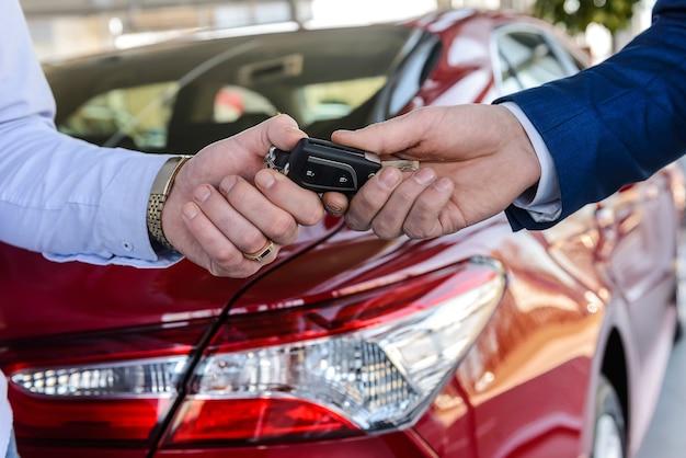 Händler, der schlüssel vom neuwagen an den kunden übergibt