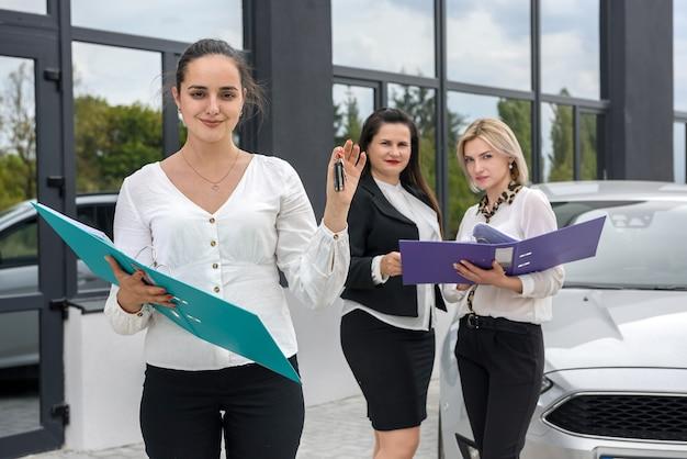 Händler hält schlüssel vom neuwagen. drei damen mit ordnern, die außerhalb showroom aufwerfen