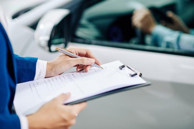Händler-manager, der kundeninformationen ausfüllt, wenn der kunde das auto vor dem kauf testet