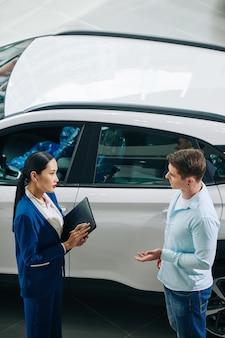 Händler-manager, der mit dem kunden spricht und nach seinen fahrzeugpräferenzen und -wünschen fragt