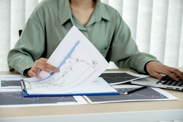 Händlerfrau analysiert aktiendiagramm und bericht, setzt ziele für das online-forex-handelsmarktmanagement.