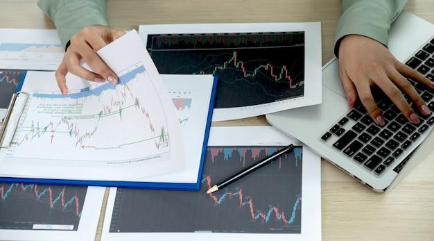 Händlergeschäftsfrau analysiert aktiendiagramm und bericht, setzt ziele für den online-forex-handelsmarkt.