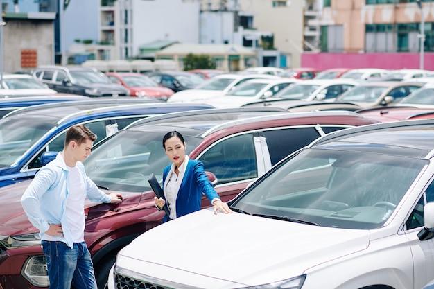 Händlerin, die dem kunden bei der auswahl eines neuen autos hilft