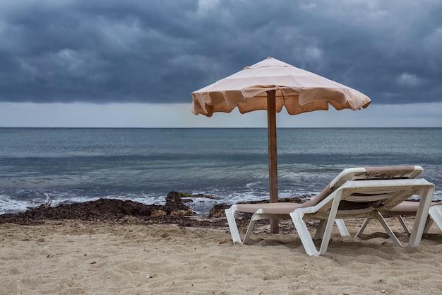 Hängematte neben sonnenschirm am stürmischen strand