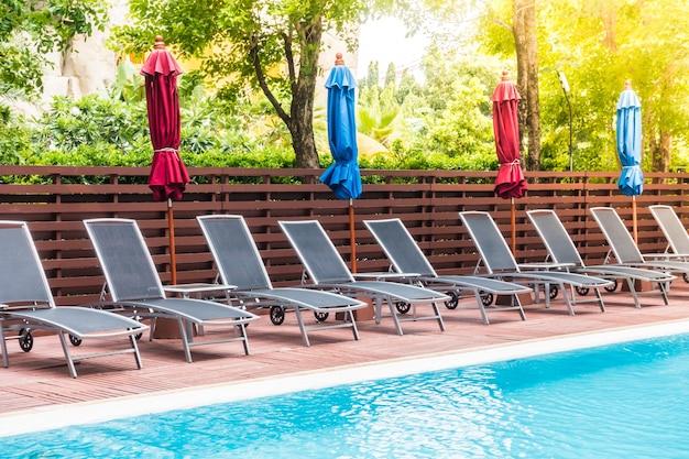Hängematten mit bunten sonnenschirmen in einem pool