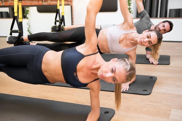 Hängende ellbogenseitenplanke trx trainiert in einer turnhalle