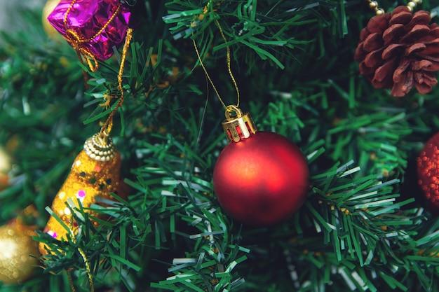 Hängende rote bälle auf kiefer verzweigt sich weihnachtsbaumgirlande und -verzierungen.