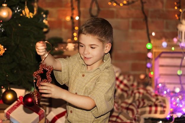 Hängende spielsachen des kleinen jungen an einem tannenbaum über der weihnachtsoberfläche