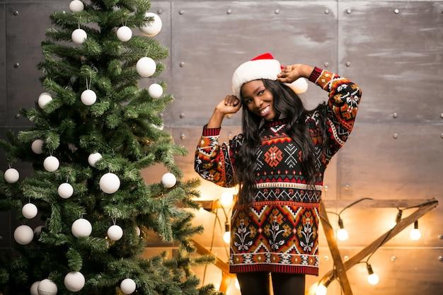 Hängende spielwaren der afroen-amerikanisch frau auf einem weihnachtsbaum
