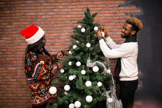 Hängende spielwaren der afroen-amerikanisch paare auf einem weihnachtsbaum