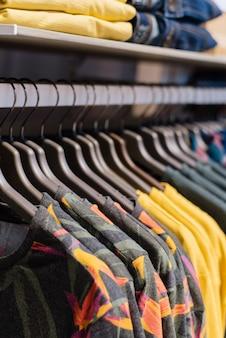 Hängende t-shirts auf kleiderbügeln im speicher