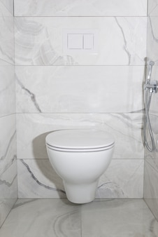 Hängende toilettenschüssel mit grauen fliesen. das innere der toilette nach der renovierung.