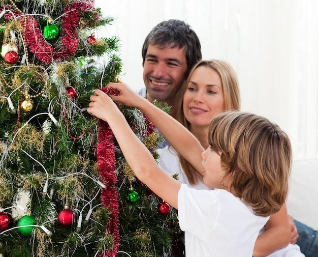 Hängende weihnachtsdekorationen des kleinen jungen mit seinen eltern