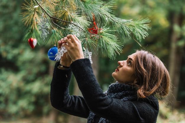 Hängende weihnachtsspielwaren der jungen frau auf zweig im wald