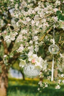 Hängendes dekor in form einer silbernen vase mit blumen, die an einem blühenden zweig eines apfelbaums im frühjahr im garten hängen
