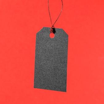 Hängendes schwarzes preisschild auf rotem hintergrund