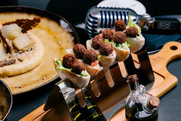 Häppchen mit fleischbällchen-salat im türkischen stil auf seitenansicht der gurken-tomaten-holzplatte