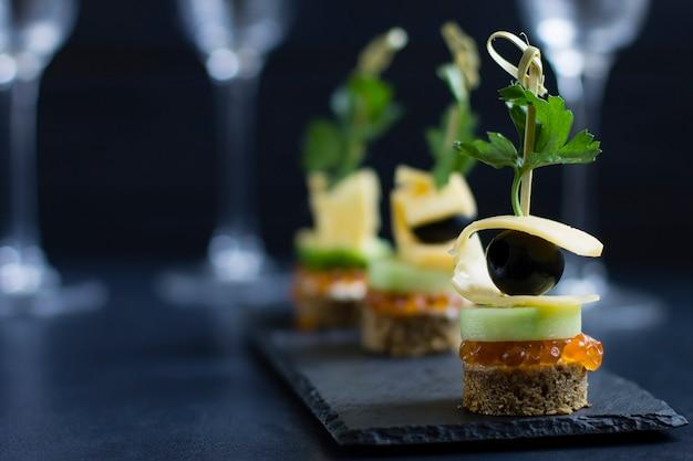 Häppchen mit käse, rotem kaviar und gurke auf einem grauen steinbrett vor dem hintergrund von gläsern.