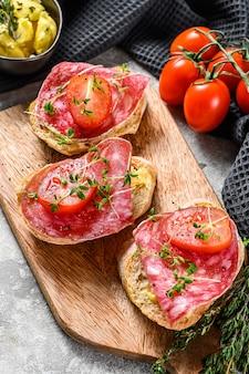 Häppchen mit salami salchichon, kirschtomaten und mikrogrün auf einem baguette. draufsicht