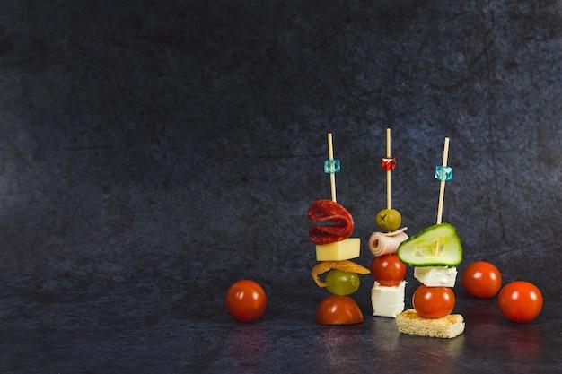 Häppchen, snacks auf dunkelblauem hintergrund, vorderansicht