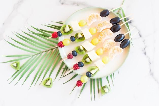 Häppchen von frischem obst und beeren auf einem teller. marmorhintergrund mit palmenzweig. festliches essen.