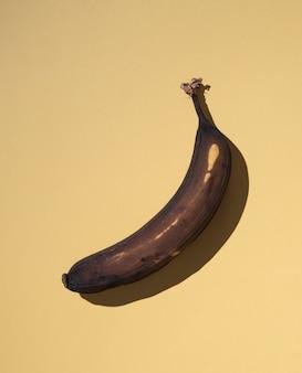Hässliche banane auf gelbem hintergrund mit hartem schatten