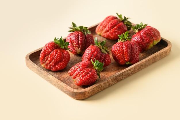 Hässliche bio-erdbeere auf beigem hintergrund