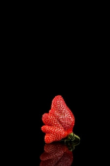 Hässliche bio-erdbeere aus eigenem anbau mit kopierraum. trendy hässliches essen. seltsame lustige unvollkommene frucht. missgestaltetes produkt, lebensmittelabfallkonzept.