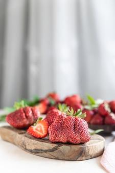 Hässliche bio-erdbeeren auf holzbrett trendige hässliche früchte