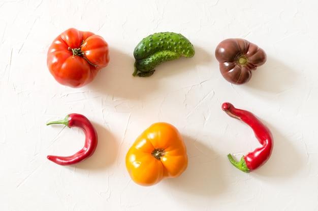 Hässliche bio-tomate, paprika, gurke auf weiß,