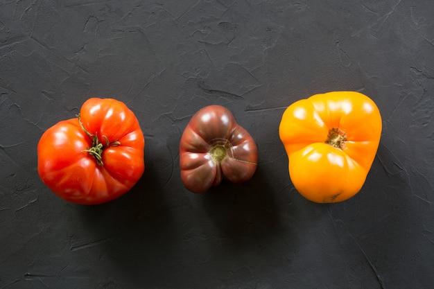 Hässliche bio-tomaten auf schwarz gesetzt,