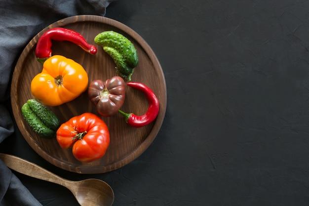Hässliche bunte tomate, pfeffer, gurke auf schwarz,