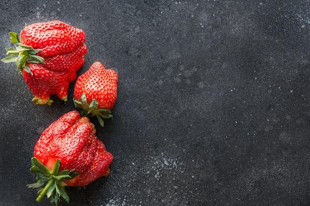 Hässliche drei reife bio-erdbeere auf schwarz.