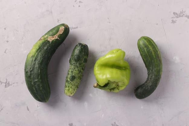 Hässliche frische gurken und pfeffer auf hellgrauem hintergrund. konzept organisches natürliches gemüse. sicht von oben