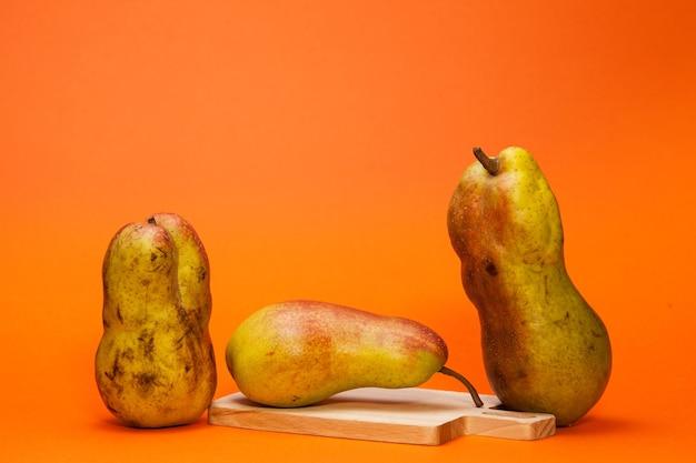 Hässliche früchte. reife birnen auf einem orangefarbenen hintergrund. das konzept der null-abfall-produktion in der lebensmittelindustrie und einer welt ohne hunger. speicherplatz kopieren.