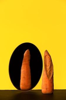 Hässliche karotte vor spiegelreflex-rückseite hässliches gemüse und obst