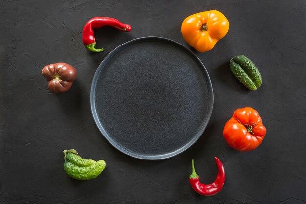 Hässliche organische bunte tomate, pfeffer, gurke auf schwarzem, organisches gemüse des konzeptes,